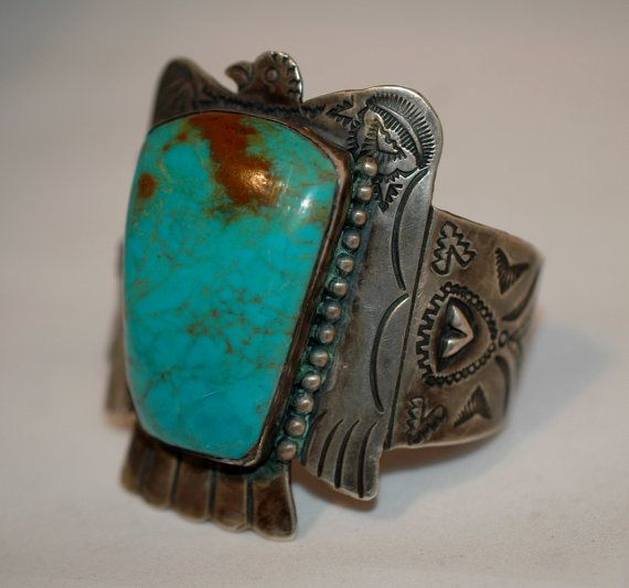 This is a gorgeous vintage Navajo museum quality coin silver or higher, Fred Harvey era Thunderbird cuff bracelet set with a huge natural magnificent Royston Mine hand cut turquoise stone! The large rounded stone measures roughly 2 by 1 1/2 wide ( measuring over the top ) and is set in an amazing winged Thunderbird that is etched and hand stamped with stunning details. The stones colors are rich and deep shades of classic Royston blue-greens and lovely brown matrix. Please note the incre...