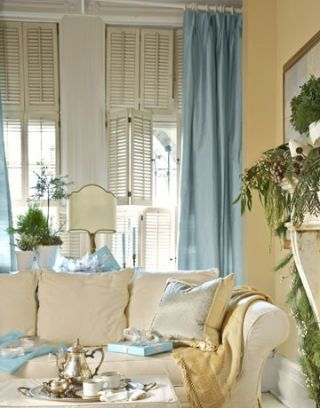 Lizabeth introduced slipcovers throughout in soft, easy fabrics, like the brushed cotton on this sofa in the den, and layered on pillows and throws to invite cuddling up. The mantel and bookshelves were painted a creamy white; the walls are Desert Tan by Benjamin Moore for contrast. Lizabeth added just a hint of dressiness with curtains of soft blue raw silk.