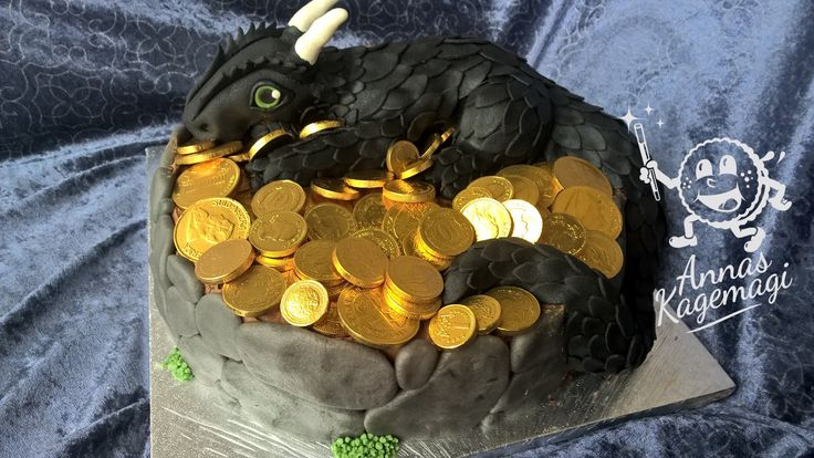 Dragon cake covered in black marzipan, laying on a bed of chocolate gold coins