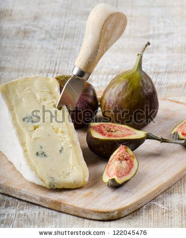 Cheese and figs on wooden platter - stock photo