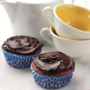 Two cupcakes in blue cases with chocolate icing next to tea cups