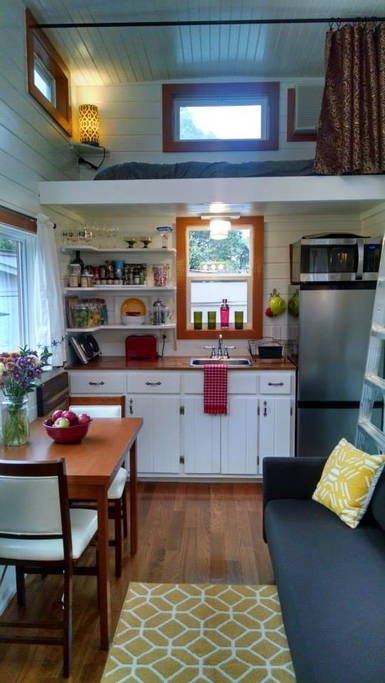 This is a tiny house on wheels in Asheville that you can vacation in using Airbnb. From the outside, you'll notice orange siding, a red door, and a covered front porch. When you go inside, yo…