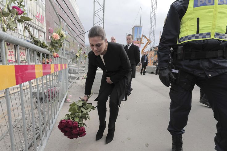Sweden's Crown Princess Victoria and her husband Prince Daniel pay respect at a makeshift memorial near the site where a truck slammed into a crowd yesterday outside a busy department store, in central Stockholm, on April 8, 2017. / AFP PHOTO