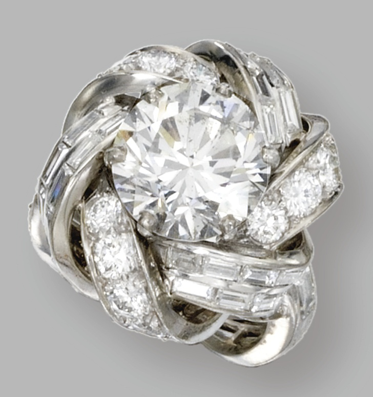 Platinum and diamond, Sterlé, Paris, circa 1960. Set in the center with a round diamond weighing approximately 4.90 carats, within a turban motif mounting set with baguette and round diamonds continuing to the interlaced band, weighing a total of approximately 4.75 carats, size 6, signed Sterlé, Paris, numbered 9549.