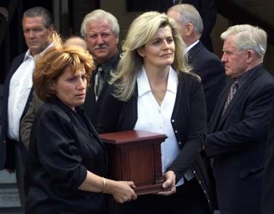 Stu Hart's daughters Georgia (right) and Ellie Neidhart carry the remains of their father after a memorial service in Calgary Thursday October 23, 2003. Wrestling patriarch Hart was remembered not only for his contribution to the sport, but also for his love of friends and family at his funeral service.