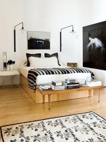 25 gorgeous bedroom decorating ideas - beautiful mix of wood accents + black and white patterns and wall art. Mid century modern bench styled with stacked books, + asymmetric black wall lamps