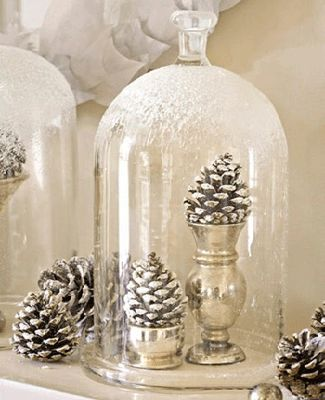 Nostalgic holiday display of pine cones & silver under a bell jar.