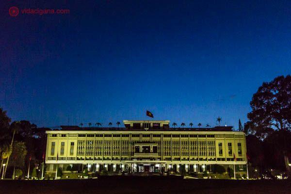 Na foto vemos o Palácio da Reunificação, prédio histórico importante que fica na Cidade de Ho Chi Minh. Foi nesse prédio que a Guerra do Vietnã acabou. O Palácio tem formato retangular, no estilo arquitetônico moderno, com uma bandeira do Vietnã no topo. A foto foi tirada durante a noite, com o céu limpo e azulado. O prédio está iluminado com uma cor amarela.