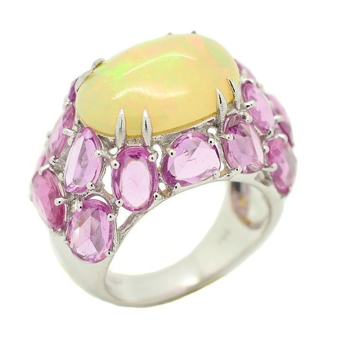 Gouden ring met 460 ct opaal en 895 ct roze saffieren  18 kt white gold ring with beautiful natural opal surrounded by pink sapphires hinting at the reflections of colours given off from the oval for an enchanting play of light! Hand made Metal: 18 kt white gold Hallmark: 750/1000 Weight: 11.30 g Central stone: 1 natural opal: 4.60 ct Accent stones: 8.95 ct natural pink sapphires Measurements of the part with the stones: 1.70 x 2.70 cm Sent with certificate of guarantee and gift box. Insured…