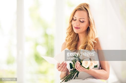 Stock Photo : Woman with roses reading greeting card