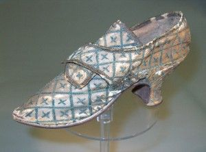 Single cream silk shoe with discoloured dark green silk embroidery all over in diagonal lattice pattern with crosses in centres, rounded pointed toe, 2 straps to fasten over tongue, 60mm high inward set Louis heel green silk ribbon bound top edge of tongue and back seam, and white kid and linen lining; c. 1745-1750. Chertsey Museum
