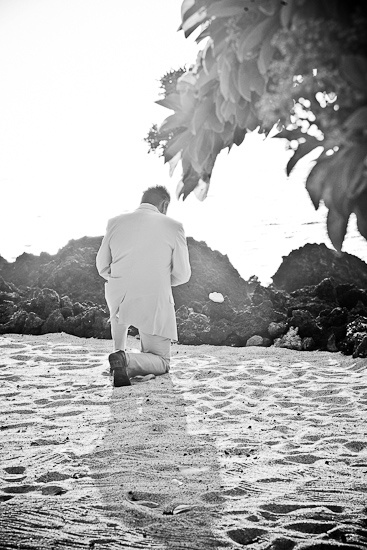 Love that the groom stop to kneel in the sand and pray before their beach wedding in Hawaii.  www.eyeexpression.com