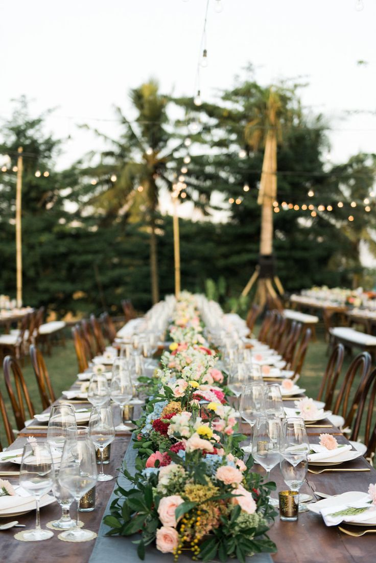 Chic sunset garden wedding reception lit up with beautiful string bulb lights and hundreds of candles scattered around the gardens. The table setting decorations consisted of colorful flowers of pink, blue and green hydrandeas, yellow, peach and pink chrysanthemums, orange bonsai berries and many colors of local roses. Tables were decorated with glass prisms filled with a flowers and golden bronze candles with matching cutlery.  Read More on SMP: http://stylemepretty.com/vault/gallery/95958