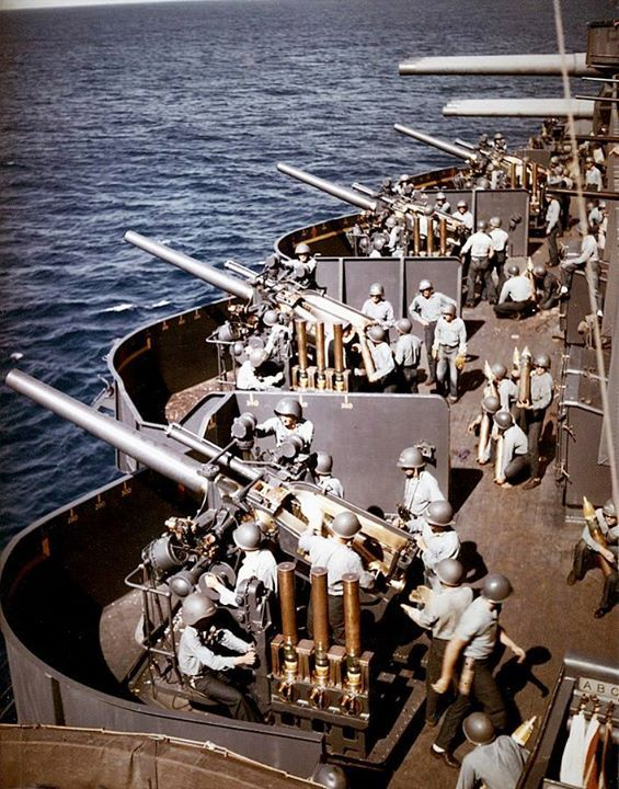"The 5""/25 (127 mm) battery aboard the U.S. Navy battleship USS New Mexico (BB-40) prepares to fire during the bombardment of Saipan 15 June 1944. Note the time-fuze setters on the left side of each gun mount each holding three ""fixed"" rounds of ammunition; the barrels of 20 mm machine guns at the extreme right; and triple the 14""/50 (34.5 cm) guns in the background."