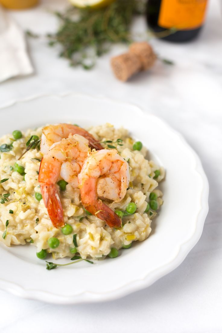 Champagne and Leek Risotto with Roasted Shrimp | With creamy rice, sautéed leeks, bubbly champagne, parmesan, and the fresh flavors of lemon zest and peas, a pot of this risotto is the perfect meal to share with the person you love. @stripedspatula