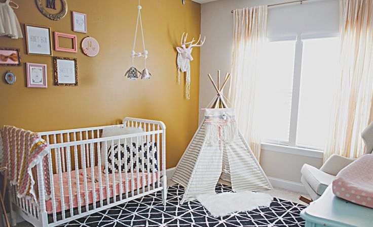Modern southwestern nursery decor featuring a mustard yellow accent wall, pink, white, and black wall decor, a knit blanket pulling the colors in the room together, pink bedding, black and white textiles and a teepee playhouse - Southwest Nursery Ideas & Decor