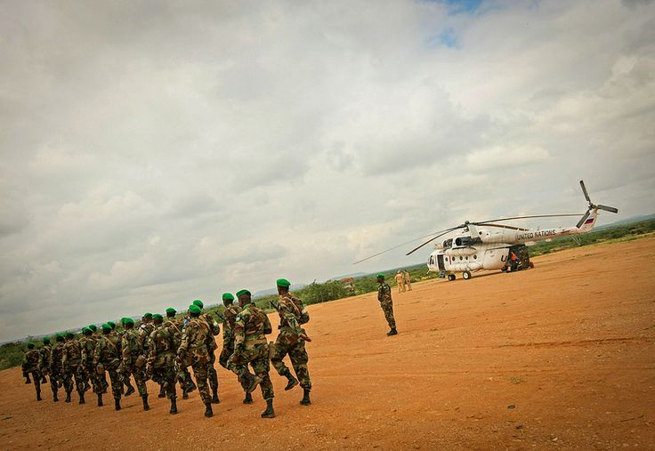 Soldiers of the Djiboutian Contingent serving with the African Union Mission in Somalia (AMISOM) march past a United Nations helicopter ahead of the arrival of further troops to the central Somali town of Belet Weyne, 16 November 2012, approx. 300km north west of the Somali capital Mogadishu. AU-UN IST PHOTO / STUART PRICE.
