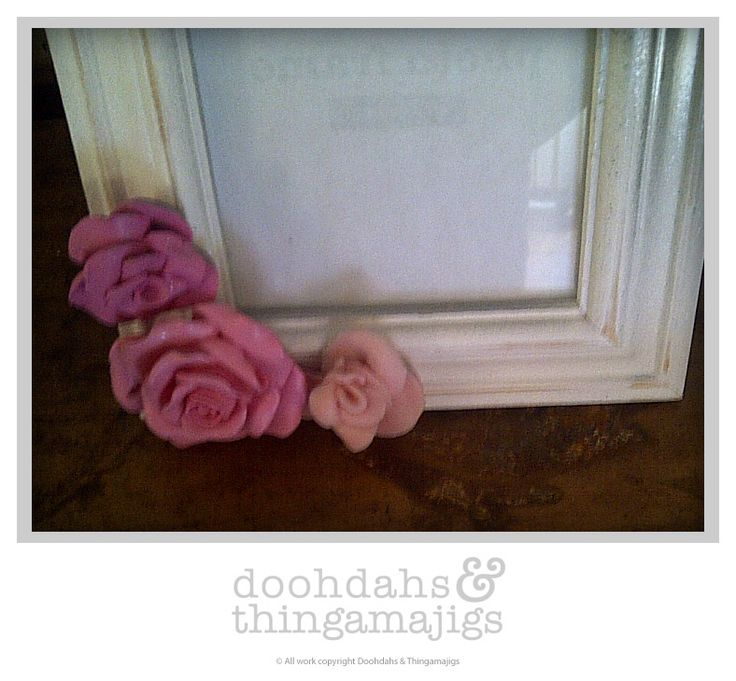 Frames decorated with odds and ends. Small frame decorated with roses. Stressed silver/pewter finish on top right side.