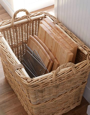 Use a large basket to store cutting boards, cookie sheets, cooking racks, etc in the kitchen