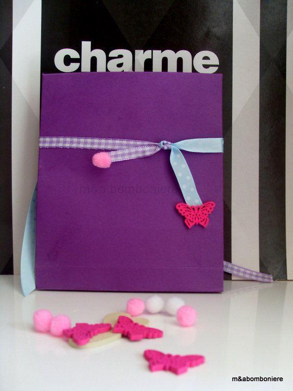 Μπομπονιέρα σε μωβ σακουλάκι με κορδέλες δύο σχεδίων, μία γαλάζια πουά και μία μωβ καρώ. Στο τελείωμά τους μια φούξια ξύλινη πεταλουδίτσα και ένα ροζ πομ πομ. Τιμή: 2,00 ευρώ.