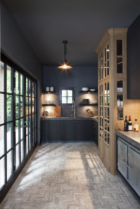 I'm so intrigued by this interior...stone, herringbone floors, large built in hutch smack dab in the middle of the kitchen, gorgeous black framed windows/doors...is that a cooler/fridge in the bottom right corner?