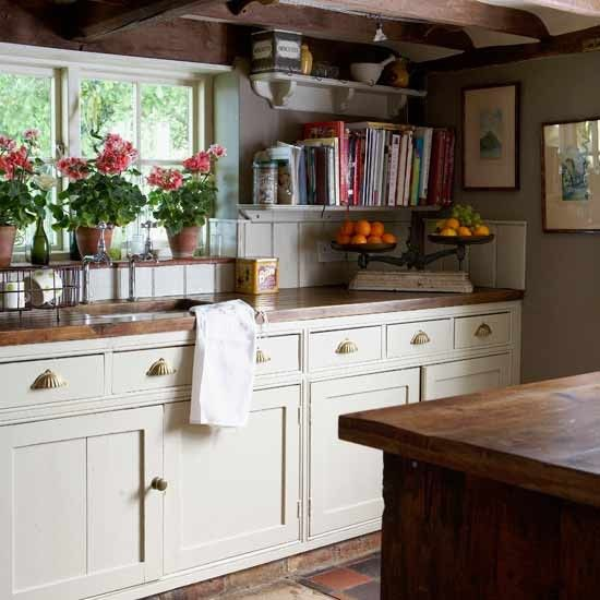 Country village kitchen    The exposed beams create a rustic country feel in this cosy kitchen. Cream-painted kitchen units are given an aged feel with vintage handles, and are teamed with warm wooden worktops. A set of antique-style scales continues the look, set against a backdrop of pale green walls. Line three plants in a row along the windowsill to add instant character.