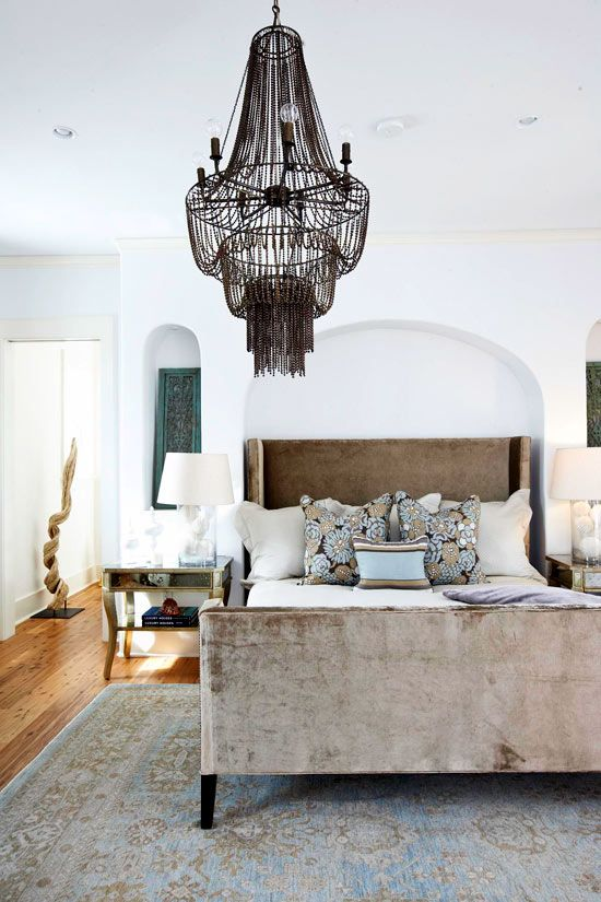 Beach-Inspired Bedroom  This bedroom was inspired by the seashore. Designer Paige Schnell upholstered the bed in a taupe cotton velvet and added a dramatic chandelier above for subtle glamour. Mirrored bedside tables lend classic elegance.  Traditional Home®