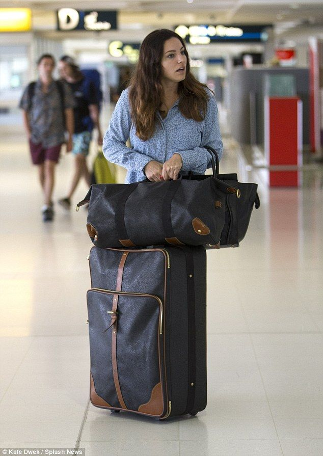 Home time: Make-up free Kelly Brook arrives at Sydney airport to catch a flight on her own...