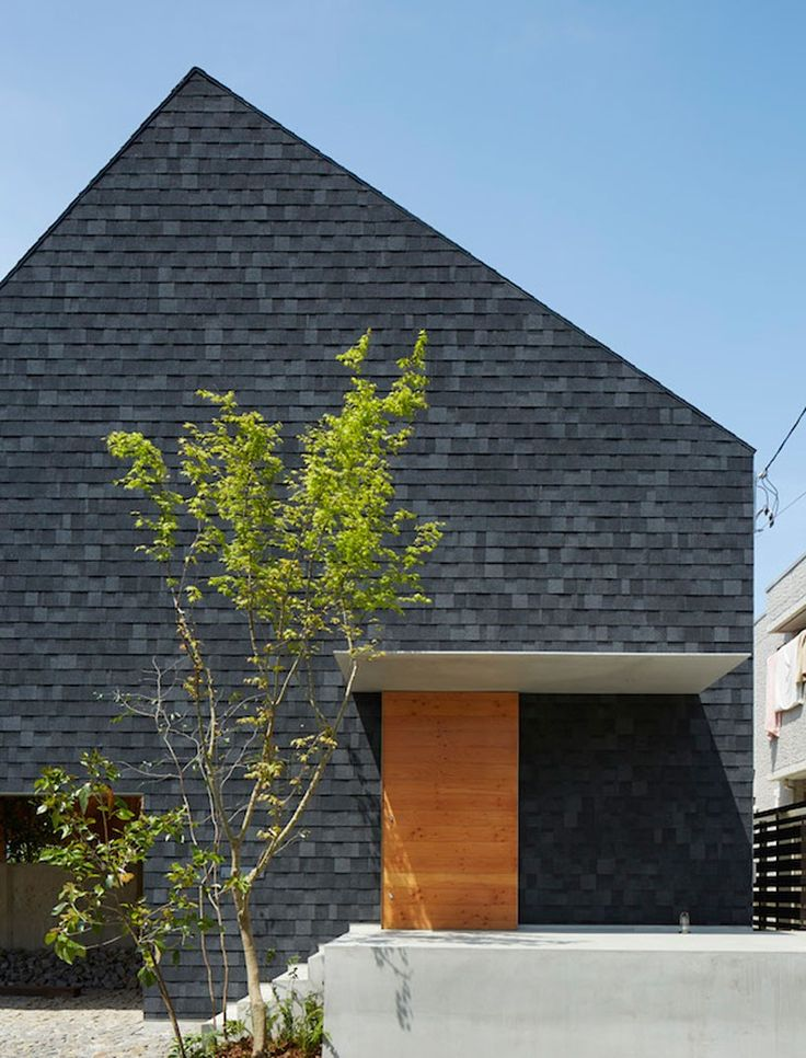 clad entirely in dark asphalt shingles, this home by suppose design office blurs the boundaries between inside and outside.