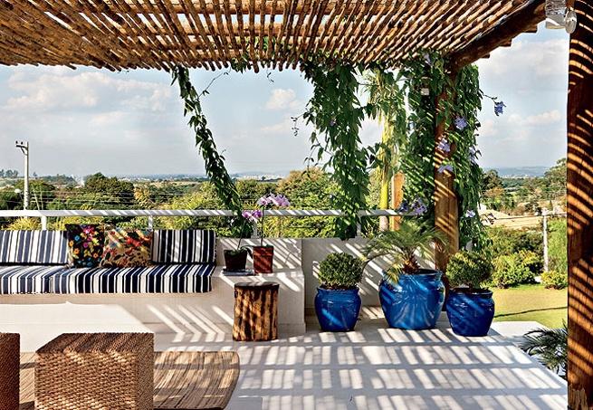 Sobre a laje da garagem desta casa de campo de 614 m², a arquiteta Lígia Resston criou o terraço com cobertura de bambu e estrutura de toras de eucalipto, nas quais cresce a trepadeira tumbérgia. Bancos de alvenaria, tapetes e pufe rústico completam a decoração