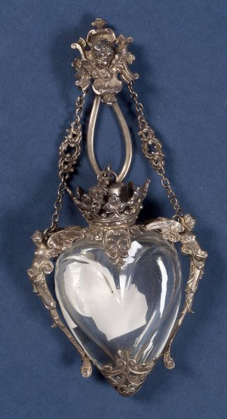Continental .800 Silver-mounted Colorless Glass Chatelaine Scent Bottle, late 19th/early 20th century, the heart shaped glass bottle with winged female herm shoulders, reticulated scroll base, coronet-form neck enclosing stopper, suspended from fancy link chain with chatelaine clip centered by cherub mask, wd. 2 3/4 in.