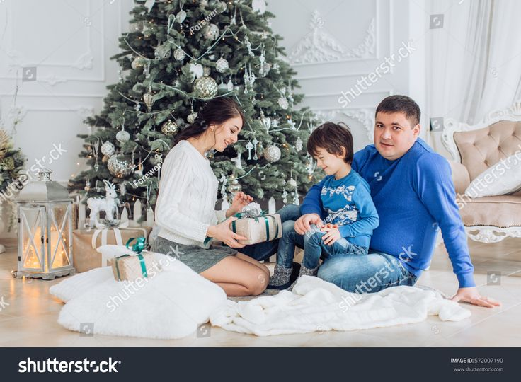 Happy boy with mather and father near Christmas tree