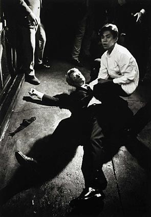 "Assassination of Robert F. Kennedy (Boris Yaro / Los Angeles Times)  June 5, 1968, Los Angeles. Busboy Juan Romero, 17, comforts Robert F. Kennedy moments after Kennedy is shot in the pantry of the Ambassador Hotel kitchen. 35 years later, Romero would tell Times' columnist Steve Lopez: ""He was looking up at the ceiling, and I thought he'd banged his head. I asked, 'Are you OK? Can you get up?'"""