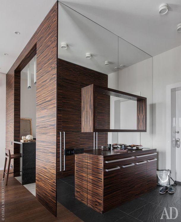 Прихожая и зона кухни. Зеркальная стена значительно расширяет границы пространства. Мебель изготовлена по эскизам дизайнера, мастерская Glooswood.