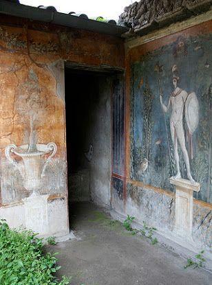 Pompeya, Casa de Venus en una concha. En la pared posterior del peristilo hay tres grandes cuadros sobre un fondo azul. La pintura de la mano izquierda es del dios Marte mostrado parado desnudo en un zócalo mientras que sostiene una lanza y un escudo. Alrededor de él el jardín foliado está lleno de aves. Erupción del año 79.