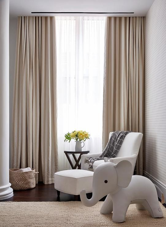 Beautiful White And Beige Nursery Boasts A Window Dressed