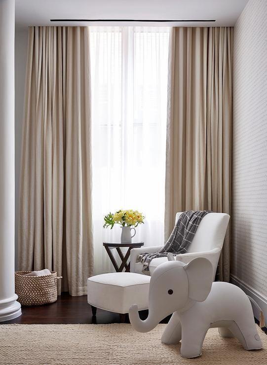 Beautiful white and beige nursery boasts a window dressed ...