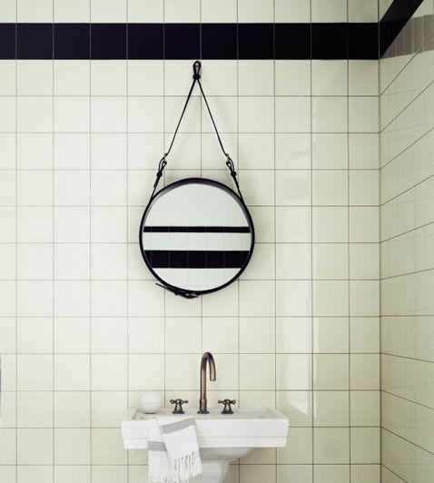 Salle de bain avec carrelage blanc et bande noire sur carrelage