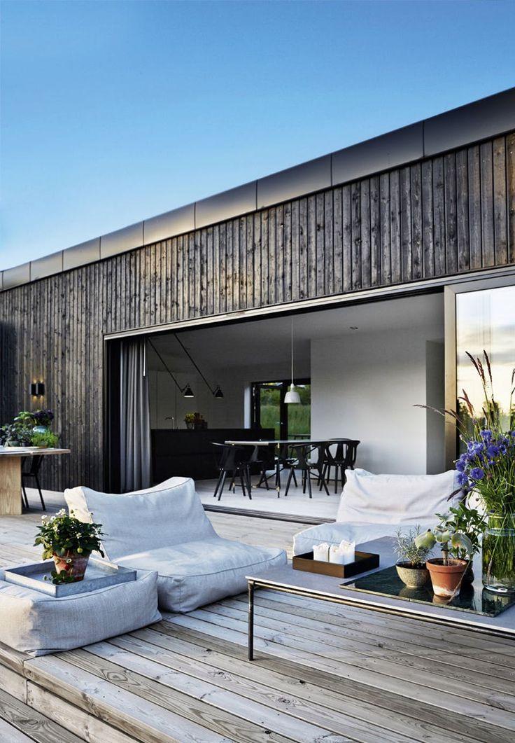 De store vinduer fra Schüco kan trækkes til side. De lave, bløde møbler er fra Broste og inviterer til loungestemning på den brede terrasse. Bordet har Emil Thorup selv designet. Til venstre ses udebordet lavet af planker fra Dinesen.