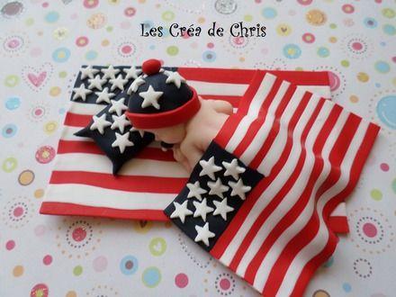 bébé fimo mixte endormi sur son drapeau Americain.      bébé mixte endormi sur son drapeau Américain, avec son oreiller, sa couverture et son bonnet dans les tons du drap - 9881415