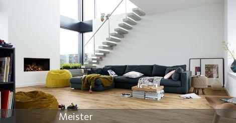 Eine offene Galerie mit einer freischwingenden Treppe bringt eine helle Atmosphäre ins Wohnzimmer. Vor dem modernen Kamin kann auf Sitzsäcken entspannt werden. Stylische Holzhocker dienen als Deko und Ablagefläche.
