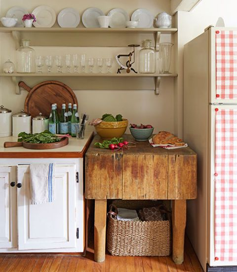 English ironstone, Picardie glassware, and an antique pharmacy scale line the kitchen shelves in this New York garden estate. The pine butcher's block came with the house.   Bright idea: A gingham paper tablecloth from West Elm, affixed with magnets, peps up a plain fridge.