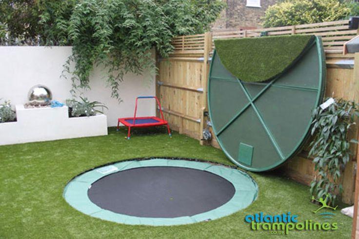 Mooi weggewerkte trampoline onder een stalen(?) deksel in een tuin met kunstgras. Linksonder het deksel zie je een katrol, waarschijnlijk bedoeld om het deksel op te tillen met een staalkabel.