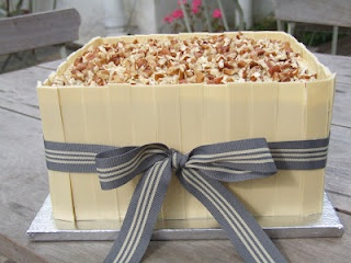 Delicious carrot cake with cream cheese frosting and white chocolate collar.