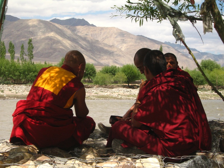 Monks sitting on the side of a river in Leh, Ladhak.