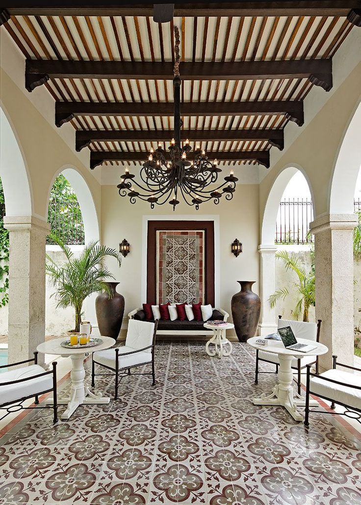 Spanish style tiles, exposed beams, and wrought iron outdoor furniture.