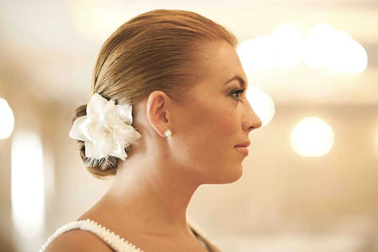 A Grace Kelly chignon, adorned with a silk flower, is the perfect hair style to accentuate your features on your special day, by drawing the attention to your face. For a Greece elegant luxury wedding! -By Mitheo Events