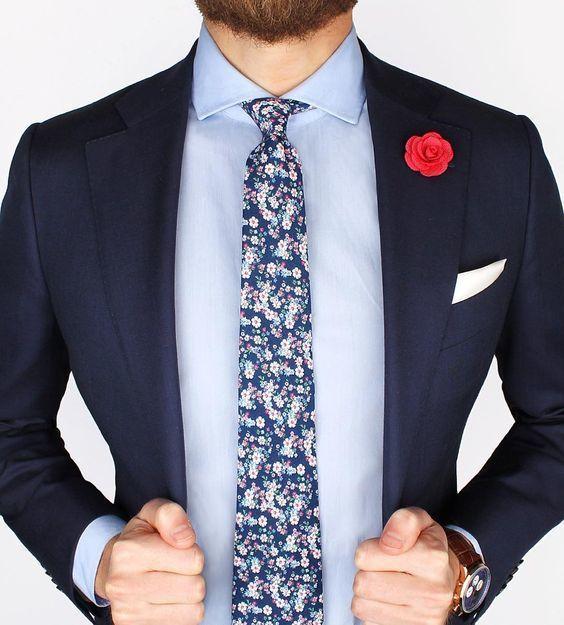 Acheter la tenue sur Lookastic: https://lookastic.fr/mode-homme/tenues/blazer-chemise-de-ville-cravate/19585 — Chemise de ville bleue claire — Cravate à fleurs bleu marine — Broche rouge — Pochette de costume blanc — Blazer bleu marine — Montre en cuir brun