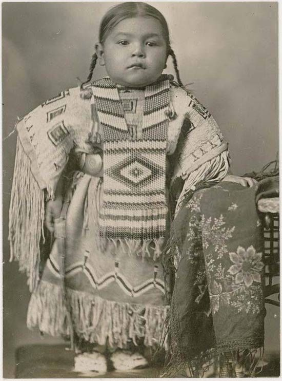 Cheyenne girl in a beaded dress and breastplate, 1915. Oklahoma.