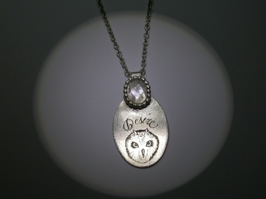 A silver necklace withe engravings and mother of pearl. Inemoni